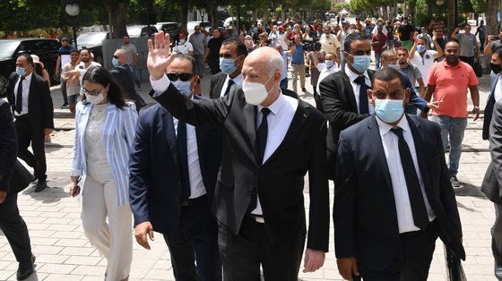 epa09386130 A handout photo made available by the Tunisian Presidency shows Tunisian President Kais Saied (C) gesturing among supports as he walks protected by security guards in Habib Bourguiba Avenue, Tunis, Tunisia, 01 August 2021. Two Members of the Parliament were reportedly arrested on 01 August brining to three the number of MPs detained since Saied sacked prime minister Mechichi and suspended the parliament on 25 July. Saied said he acted within the constitution as US Secretary of State Antony Blinken called for the return 'to the democratic path' in the country.  EPA/PRESIDENCY OF TUNISIA HANDOUT  HANDOUT EDITORIAL USE ONLY/NO SALES