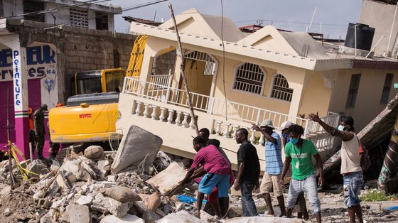 epa09423987 Peope attempt a rescue after 7.2 earthquake that occurred on 14 August, in Les Cayes, Haiti, 21 August 2021. The earthquake left some 2,200 dead and 12,000 wounded.  EPA/ORLANDO BARRIA