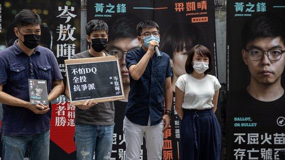 Os candidatos primários pró-democracia para a eleição legislativa Lester Shum (2ºE), Joshua Wong (2ºD) e Jannelle Leung (D), Hong Kong, julho de 2020
