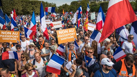 epa09447286 Protesters hold French flags and Anti Pass posters as they gather during a demonstration held by right-wing party 'Les Patriotes' against the COVID-19 sanitary pass which grants vaccinated individuals greater ease of access to venues, in Paris, France, 04 September 2021. Thousands of French demonstrators have taken to the streets in several cities across the country to protest against measures to curb the spread of coronavirus.  EPA/CHRISTOPHE PETIT TESSON