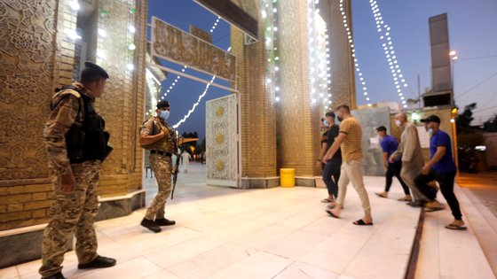 epa09354337 Iraqi policemen stand guard as Iraqi Sunni Muslims arrive to perform Eid Al-Adha prayers amid the COVID-19 pandemic at the  Abu Hanifa mosque in Baghdad's Adhamiya district, Iraq, 20 July 2021. Eid al-Adha is the holier of the two Muslims holidays celebrated each year; it marks the yearly Muslim pilgrimage (Hajj) to visit Mecca, the holiest place in Islam. Muslims slaughter a sacrificial animal and split the meat into three parts, one for the family, one for friends and relatives, and one for the poor and needy.  EPA/AHMED JALIL