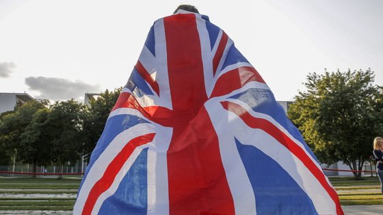 epa07784683 A visitor wrapped in a British flag stands in front of the Chancellery duringt the visit of British Prime Minister Boris Johnson in Berlin, Germany, 21 August 2019. Prior to the G7 summit in Biarritz form 24 to 27 August 2019, Johnson meets Angela Merkel and on the next day French President Emmanuel Macron. In the talks, Johnson is expected to try to resume the Brexit talks, so that it will not come to a 'no deal' exit of the United Kingdom from the EU on 31 October 2019.  EPA/MICHELE TANTUSSI