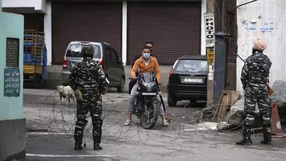 epa09195995 Indian paramilitary soldiers stop a Kashmiri motorcyclist near barbed wire set up as barricade during lockdown in Srinagar, the summer capital of Indian Kashmir, 13 May 2021. Kashmiri Muslims offer Eid prayers at heritage Aali Masjid and mosques in interior areas while following Covid guidelines. Most of major mosques and shrines in Indian Kashmir remained closed in view of Covid lockdown enforced by authorities to prevent spread of Coronavirus pandemic.  EPA/FAROOQ KHAN