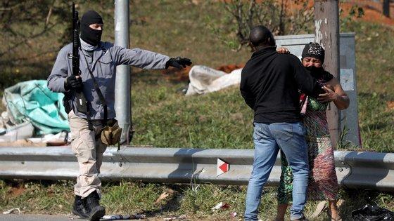 Um homem acalma uma mulher que foi atingida por uma bala de borracha, durante saques em Mobeni, Durban, nesta quinta-feira