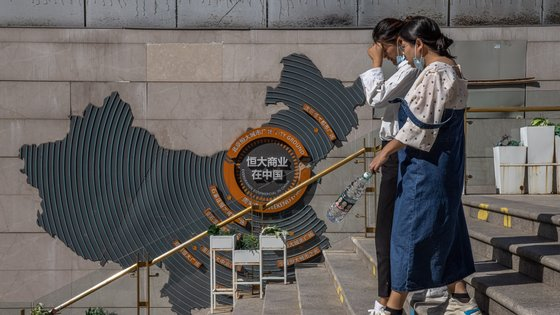epa09481151 Women walk past a map showing Evergrande commercial hubs in China at Evergrande city plaza, in Beijing, China, 22 September 2021.  China's real estate developer Evergrande Group said it would pay scheduled interest on one of the bonds due on 23 September, giving some relief to the troubled shares of the company since the group announced concern it might not be able to meet its financial obligations. Hong Kong markets are closed for public holiday, however the company's shares listed in Frankfurt rose by almost 20 percent on the reports.  EPA/ROMAN PILIPEY