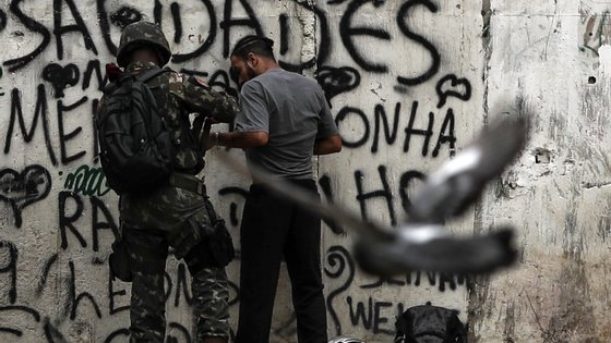 epa07035265 aA local man is searched as armed military soldiers patrol in a neighbohood in Rio de Janeiro, Brazil, 20 September 2018. Nearly 450 members of the Armed Forces participate in an operation against drug trafficking at the Jacarezinho slum in Rio de Janeiro.  EPA/ANTONIO LACERDA