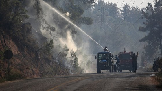 epa09383267 People try put out a wildfire burning at a rural area of Marmaris district of Mugla, Turkey, 31 July 2021. According to a statement by the Turkish government's Disaster and Emergency Management Presidency (AFAD) released on 30 July 2021, at least three people lost their lives and some 271 others were affected by blazes that swept through the country's southern coast.  EPA/ERDEM SAHIN