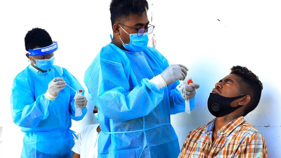 epa09407850 A health worker collects a specimen sample from a man during a COVID-19 swab test in Dili, East Timor, known also as Timor Leste, 10 August 2021. East Timor has officially recorded more than 10,000 coronavirus disease (COVID-19) cases since the beginning of the pandemic.  EPA/ANTONIO DASIPARU