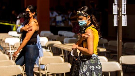 Duas mulheres pressionam o braço no local onde lhes foi administrada a vacina contra a Covid-19