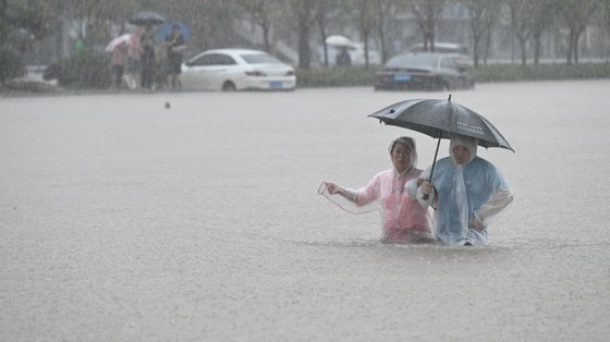 Em Zhengzhou, as ruas transformaram-se em canais de água, com o rápido fluxo de água a arrastar pessoas, veículos e apartamentos