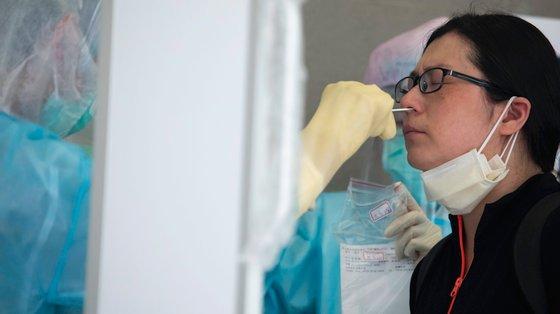 Um técnico recolhe uma amostra da nasofaringe numa mulher para realizar um teste PCR à presença do coronavírus