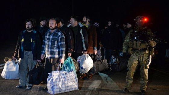 Prisioneiros esperavam pela troca, vigiados por soldados armados