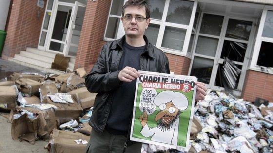 Charb (na foto) em frente à sede do jornal que, em 2011, ficou destruída depois de um ataque de uma bomba incendiária