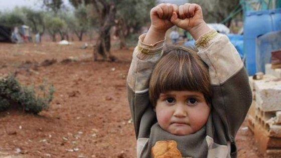 A menina abriu os braços em rendição ao confundir a máquina fotográfica com uma arma