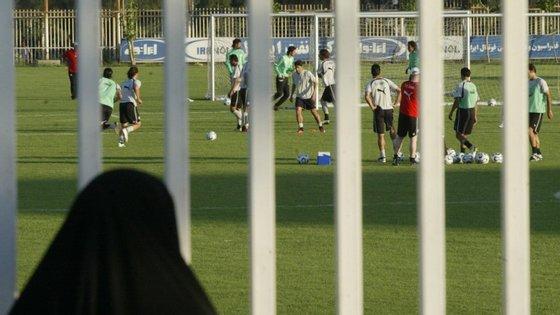 Em 2006, uma iraniana assiste ao treino da seleção, estando impedida de entrar no estádio para ver o jogo