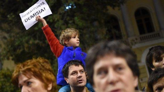 Menino ergue cartaz a pedir a demissão do primeiro-ministro, Victor Ponta, e do ministro do Interior, Gabriel Oprea