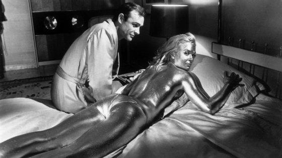 """Sean Connery e a atriz inglesa Shirley Eaton, coberta de ouro, durante as filmagens de """"Goldfinger"""", realizado por Guy Hamilton."""