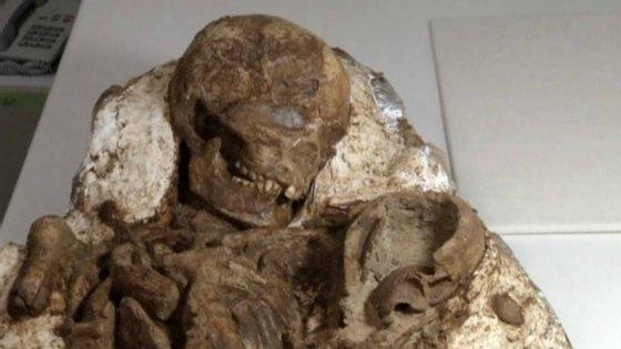O fóssil da mãe a olhar para a criança nos braços