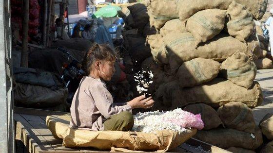 Uma menina paquistanesa a limpar alho num mercado em Lahore.