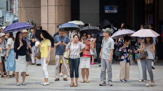 Com as temperaturas a ultrapassarem frequentemente os 35º C, a população opta por se proteger do Sol com chapéus-de-chuva