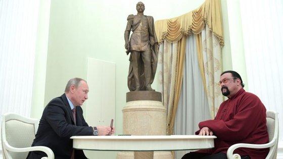 O Presidente russo, Vladimir Putin, a assinar o passaporte russo de Steven Seagal (à direita)