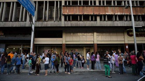 Pessoas aguardam no exterior dos edifícios evacuados em Caracas.