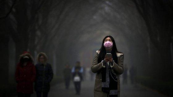 Uma mulher, na China, em Pequim, em 2015, enquanto uma nuvem de poluição atravessava a cidade