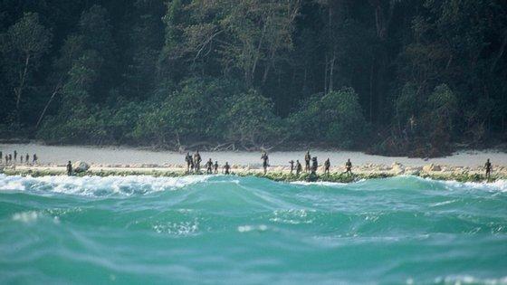 Sentineleses à beira da água na ilha Sentinela do Norte, na Índia