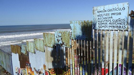 """Um cartaz onde se lê em português """"Nenhum Obstáculo nos Pode Impedir Alcançar os Nossos Sonhos; Somos Mexicanos, Somos Imparáveis."""" preso ao muro que divide a fronteira entre o México e os Estados Unidos, em Tijuana, México, 7 de dezembro de 2018"""