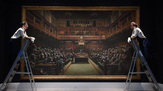 O quadro tem a dimensão de 4,20 por 2,50 metros e nele todas as bancadas da Câmara dos Comuns estão ocupadas por primatas
