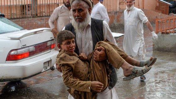 Um homem carrega para o hospital uma das vítimas do ataque desta sexta-feira