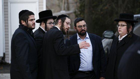 Membros da comunidade judaica de Monsey à porta da casa do rabino onde ocorreu o ataque no sábado à noite