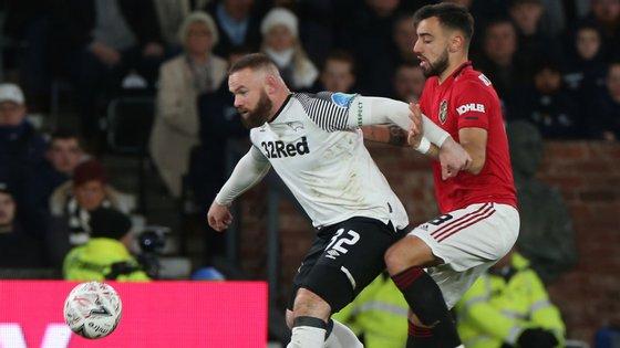 Bruno Fernandes disputa a bola com Wayne Rooney, num duelo entre antiga e atual referência do Manchester United