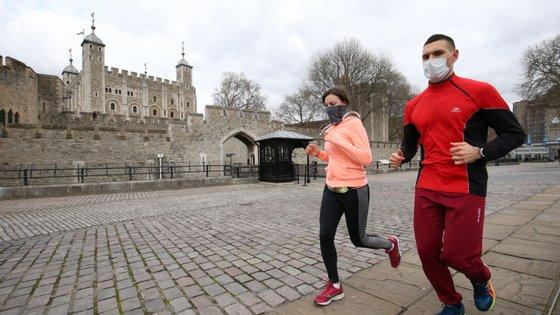 Uma mulher e um homem correm junto à Torre de Londres, no Reino Unido