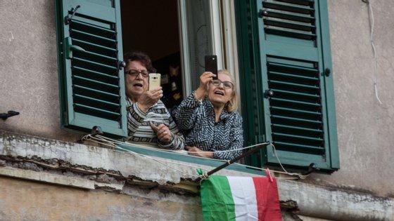 Duas mulheres assistem a uma iniciativa de solidariedade nas ruas de Roma enquanto cumprem o isolamento obrigatório