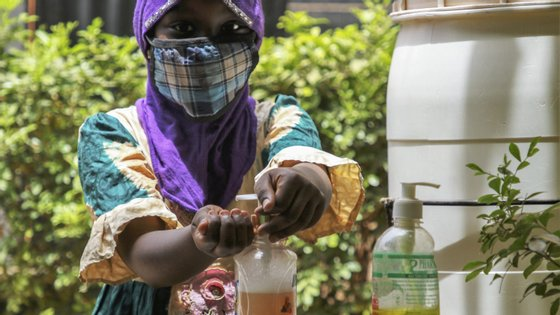 Mulher de máscara e a lavar as mãos no Burkina Faso