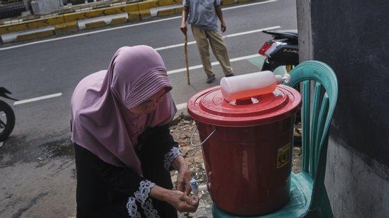 Uma mulher lava as mãos num sistema improvisado num bairro de Jacarta