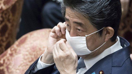 O primeiro-ministro japonês com uma das máscaras reutilizáveis que tem sido distribuída