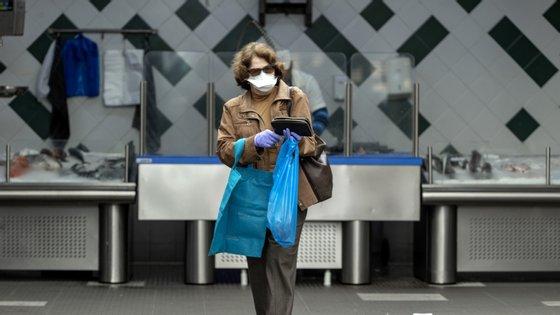 Uma mulher protegida com máscara e luvas faz compras no Mercado da Graça