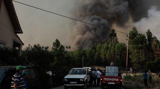 Populares observam um incêndio que lavra em Oleiros, Castelo Branco, 14 de setembro de 2020. O incêndio que deflagrou em Proença-a-Nova no domingo e que lavra hoje com intensidade em Oleiros já está próximo do Rio Zêzere, afirmou hoje o presidente da Câmara. Segundo a Autoridade Nacional de Emergência e Proteção Civil estão neste momento a combater o incêndio 1041 operacionais no terreno, apoiados por 343 veículos e oito meios aéreos. PAULO CUNHA /LUSA