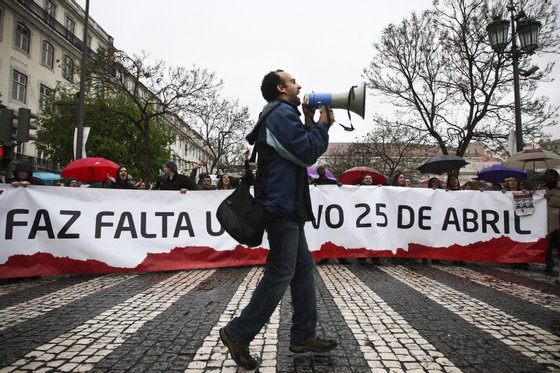 """A man shouts slogans in front of a banner reading """"A new 25th April is needed""""  as he marches with other demonstrators in downtown Lisbon on April 25, 2012, during a demonstration to celebrate the 38th anniversary of the revolution day in Portugal. AFP PHOTO/ PATRICIA DE MELO MOREIRA        (Photo credit should read PATRICIA DE MELO MOREIRA/AFP/GettyImages)"""