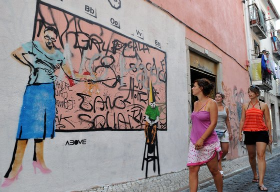 """TO GO WITH AFP STORY IN FRENCH BY ANNE LE COZ --- Three bystanders look at a graffiti on the wall of a building of Bairro Alto, on August 15, 2008, a neighbourhood of Lisbon. Several well-known graffiti's artists painted the walls of this bohemian neighbourhood, creating an """"Ephemeral Museum"""".   AFP PHOTO/ FRANCISCO LEONG (Photo credit should read FRANCISCO LEONG/AFP/Getty Images)"""