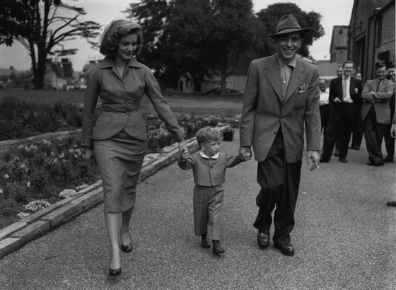 Film star Humphrey De Forest Bogart (1899-1957) and his fourth wife Lauren Bacall walk their son Stevie through the grounds of Isleworth film studios, where he has been working on 'The African Queen'.   (Photo by Central Press/Getty Images)