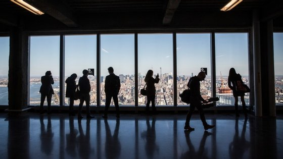 NEW YORK, NY - NOVEMBER 03:  Members of the media explore a model office, used to exhibit what a business space could look like on the 63rd floor of  One World Trade Center, which opens for business today, on November 3, 2014 in New York City. The skyscraper is 104 stories tall and cost $3.9 billion; it opens more than 13 years after the terrorist attacks of September 11, 2001, destroyed the original World Trade Center buildings. Officials say the building is currently at 60% occupancy, with Conde Nast as one of the first major tenants to move in.  (Photo by Andrew Burton/Getty Images)