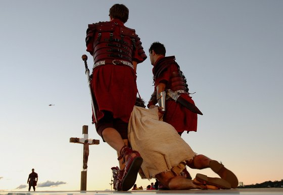 """Jesus (below) is dragged to the cross during a re-enactment at World Youth Day at Barangaroo in Sydney on July 18, 2008. The """"stations of the cross"""" re-enactment of the last days of Jesus Christ's life, was being held at some of Sydney's most famous sites and had been expected to draw between 350,000 and 450,000 spectators, organisers said.   AFP PHOTO / Greg WOOD (Photo credit should read GREG WOOD/AFP/Getty Images)"""