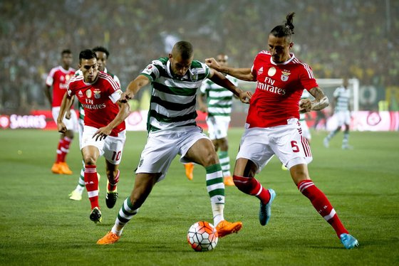 epa04878682 Benfica player Ljubomir Fejsa (R) vies for the ball with Islam Slimani (C) of Sporting Clube de Portugal during the 'Candido de Oliveira' Supercup match held at Algarve Stadium in Faro, Portugal, 09 August 2015. EPA/JOSE SENA GOULAO