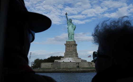 NEW YORK, NY - OCTOBER 12: Tourists look on as they pass near the Statue of Liberty while on a cruise through New York harbor on October 12, 2013 in New York City. The Statue of Liberty is set to reopen tomorrow after been closed for several days due to the government shutdown . (Photo by Kena Betancur/Getty Images)