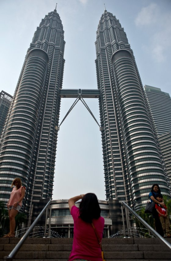 To go with Ukraine-Russia-crisis-aviation-Malaysia-tourism,FOCUS by Bhavan Jaipragas Tourists pose at the Petronas Twin Towers in Kuala Lumpur on July 23, 2014. An unprecedented second major aviation disaster in four months could further associate Malaysia with calamity in the eyes of travellers, observers warn, putting the tropical destination's vital tourism sector at risk. AFP PHOTO/ MANAN VATSYAYANA (Photo credit should read MANAN VATSYAYANA/AFP/Getty Images)