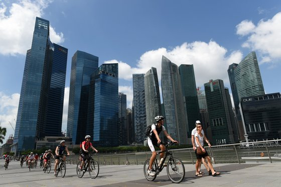 """A group of Westerners ride their bicycles along the promenade at Marina Bay in Singapore on January 13, 2015. The New York Times recently published its """"52 Places to go in 2015"""", and Singapore came in at number six on their list, Singapore media reported online. AFP PHOTO / ROSLAN RAHMAN (Photo credit should read ROSLAN RAHMAN/AFP/Getty Images)"""