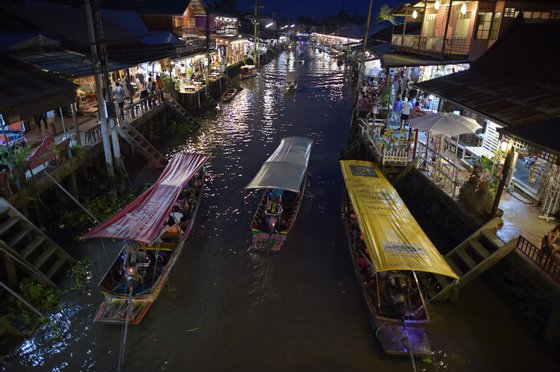 This picture taken on March 28, 2015 shows boats carrying visitors along the Amphawa canal, a small tributary of the Mae Khlong River, in Samut Songkhram province some 80 kilometers west of Bangkok. The canal turns into a floating market every weekend when crowds of Bangkokians flock to feast on bargain seafood. The visitors fill every inch of the steps surrounding the canal to pick out crabs, squids, clams, fish or shrimps from moored boats fully kitted with stoves and kitchen utensils. Cooks roast their catch in the open air before waiters carefully carry plates of food along boat edges to their customers. Others stay put, delicately swinging their freshly prepared meals in baskets hanging from long bamboo sticks directly onto tables. AFP PHOTO / Christophe ARCHAMBAULT (Photo credit should read CHRISTOPHE ARCHAMBAULT/AFP/Getty Images)